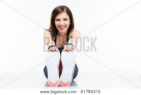 Happy young sporty woman sitting on the floor and stretching isolated on a white background. Looking at camera