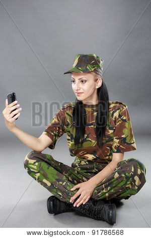 happy woman soldier looks at a mobile phone