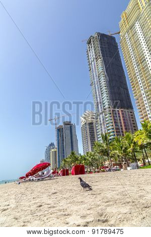 People Enjoy The Beach At Sunny Isles Beach Near The Pier