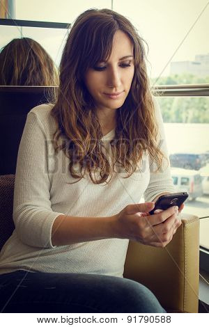 Young Cheerful Woman Sitting In Restaurant Using Smartphone.