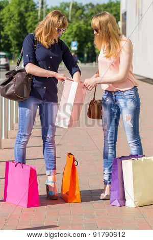 Young Woman Exploring Their Shopping Bag On The Street