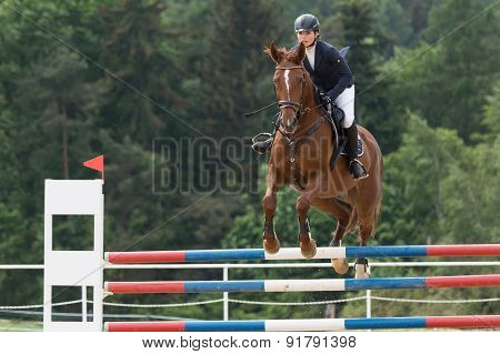 Young  Horsewoman In Black Jacket Is Jumping