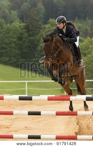 Closeup View Of Dark Haired Horsewoman Jumping