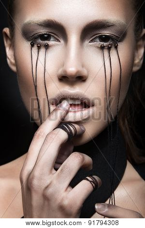 Beautiful girl with creative makeup in Gothic style and the threads of eyes. Art beauty face.