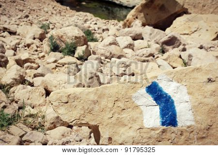 Hiking trail marker painted on a stone in rocky desert area