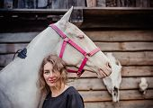 stock photo of horse face  - Young woman and her cremello horse on the background of horse and deer skulls - JPG