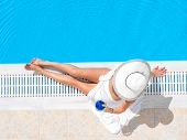 picture of woman bikini  - Young woman in bikini with a straw hat by the swimming pool - JPG