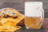 stock photo of potato chips  - Beer with foam in glass mug and potato chips in bag on wooden table - JPG