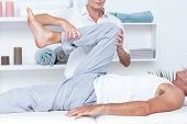 pic of physiotherapist  - Physiotherapist doing leg massage to her patient in medical office - JPG