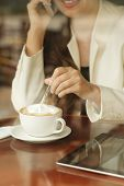 image of coffee crop  - Cropped image of woman having cup of coffee and talking on the phone - JPG