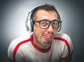 stock photo of sticking out tongue  - Young man make a funny face. Young freak guy with headphones  sticking out her tongue in front of vignetting darg gray background - JPG