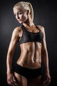pic of muscle builder  - Beautiful athletic woman showing muscles on dark background - JPG