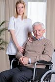 stock photo of older men  - Young beautiful caregiver and older disabled man on wheelchair - JPG