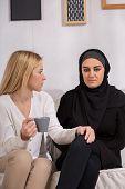 stock photo of arabic woman  - Sad arab woman meeting with european friend - JPG