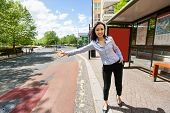 stock photo of hail  - Full length beautiful businesswoman hailing taxi on street - JPG