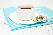 stock photo of apricot  - Cup of tea and spring apricot blossom on a wooden background - JPG