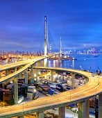 stock photo of hong kong bridge  - Container Cargo freight ship with working crane bridge in shipyard under Stonecutters highway bridge at sunset for Logistic Import Export - JPG