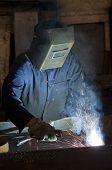 stock photo of tig  - Working man with helmet shield on his head is welding steel construction - JPG