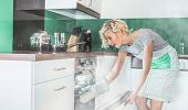 pic of vapor  - Surprised housewife frying or roasting in a oven - JPG
