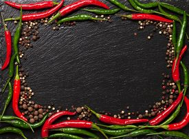 image of peppercorns  - Chili pepper and peppercorn on black stone table with copy space - JPG