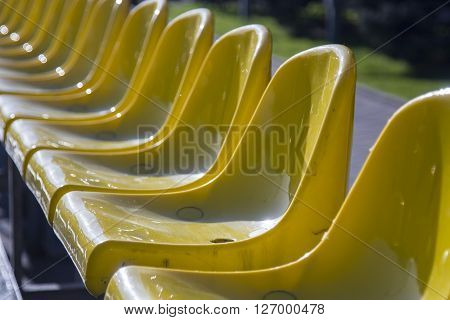 Plenty of yellow plastic seats at stadium