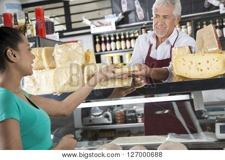Happy Salesman Selling Cheese To Female Customer