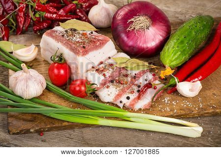salted lard with spices and vegetables on woden cutting board