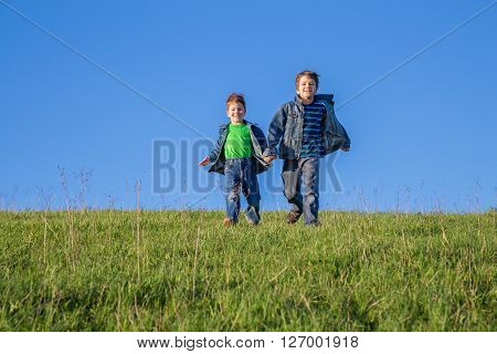 Two happy boys running together on green hill against blue sky