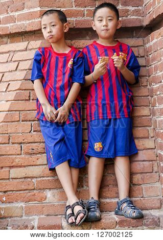 SPAIN, BARCELONA, JUNE, 28, 2015 -Two young Asian child in the form of the national team of Barcelona on a background of a brick wall in Barcelona, Catalonia, Spain