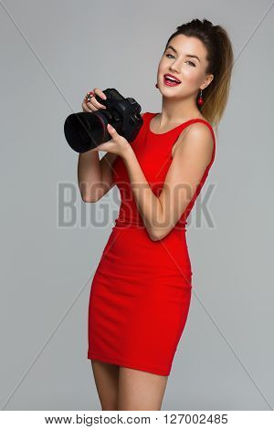 Beautiful photographer woman holding dslr camera with portrait lense. Happy expression. Over grey background. Copy space.