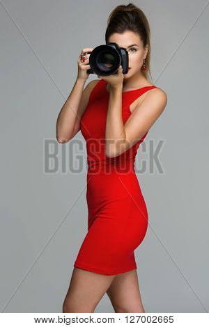 Beautiful photographer woman taking picture with dslr camera with portrait lense. Over grey background. Copy space.