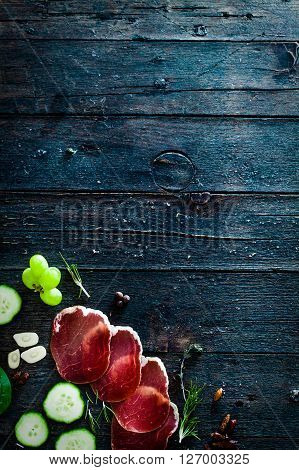 Italian ham prosciutto and salami. Ingredients for bruschetta crostini or sandwich bar. Rustic top view of ingredients. Ham with vegetables and spices