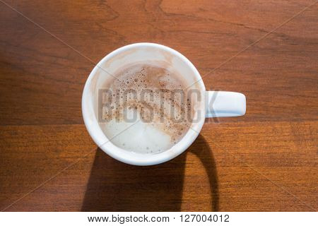 Close focus from top view on white cup of hot mocha coffee which depleted. It put on wooden brown table and bright light came from the top.