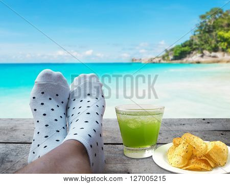 feet on wooden floor with glass of apple juice and potato chips over beach background Relaxtion on vacation concept