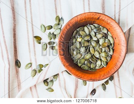 Raw Pumpkin Seeds In A Clay Plate, Linen Napkin, Top View