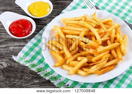 Tasty french fries on a white plate with mustard and tomato sauce in a gravy boat on wooden table background close-up