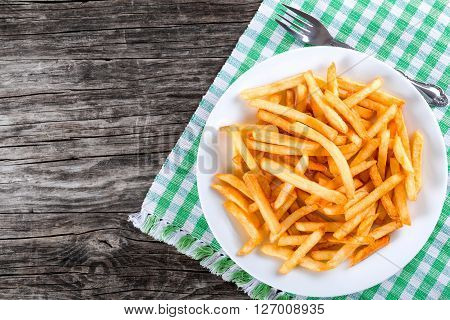 Tasty french fries on white plate on table napkin with fork on wooden background blank space left top view