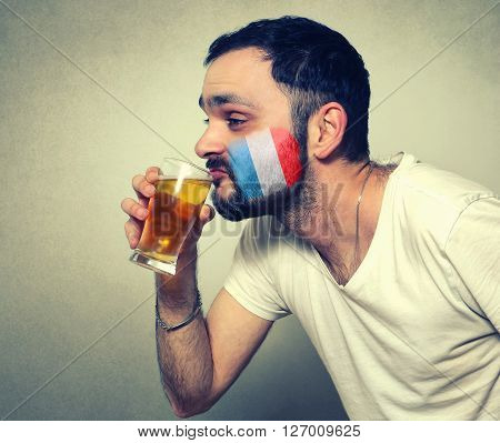 funny bearded sport fan of France drinking beer