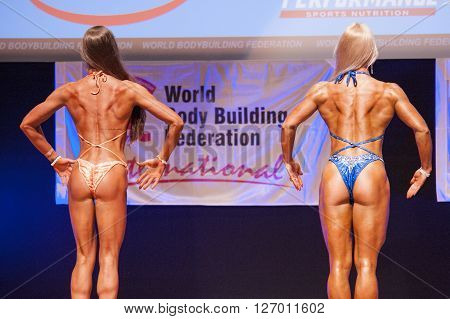 MAASTRICHT THE NETHERLANDS - OCTOBER 25 2015: Female fitness models Kinga Golebiewska and another competitor flex their muscles and show their best physique in a back pose on stage at the World Grandprix Bodybuilding and Fitness of the WBBF-WFF