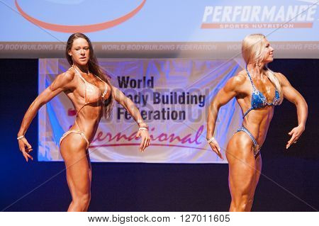 MAASTRICHT THE NETHERLANDS - OCTOBER 25 2015: Female fitness models Kinga Golebiewska and another competitor flex their muscles and show their best physique in a side pose on stage at the World Grandprix Bodybuilding and Fitness of the WBBF-WFF
