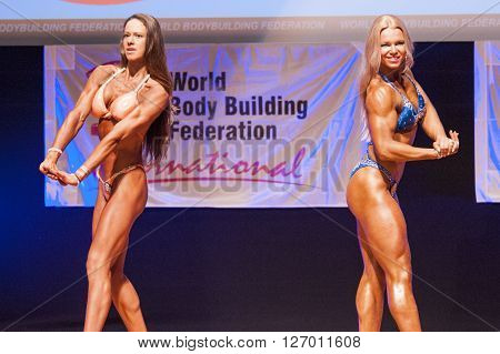 MAASTRICHT THE NETHERLANDS - OCTOBER 25 2015: Female fitness models Kinga Golebiewska and another competitor flex their muscles and show their best physique in a chest pose on stage at the World Grandprix Bodybuilding and Fitness of the WBBF-WFF