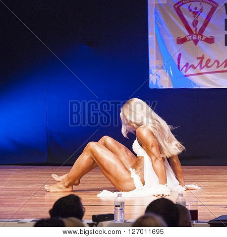 MAASTRICHT THE NETHERLANDS - OCTOBER 25 2015: Female fitness model Kinga Golebiewska flexes her muscles and shows her best physique in a dans act on stage at the World Grandprix Bodybuilding and Fitness of the WBBF-WFF on October 25 2015 at the MECC