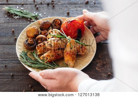 Waiter serving a shish kebab with tomato and mushrooms on wooden background. Eastern cuisine dish flat lay. Food photography of Eastern cuisine dish shish kebab on white plate.