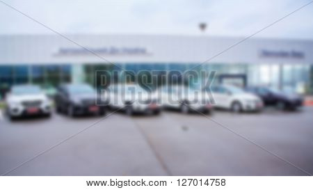 Abstract blurred photo of motor show, car show room, blur color tone