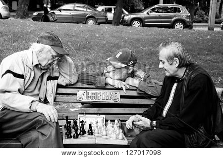 Lviv Ukraine - September 13 2014: Three senior old men friends sitting on bench in park outdoor playing chess together in park outdoor black and white