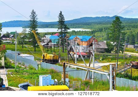 SATKA RUSSIA - AUGUST 16 2009. The territory of Zyuratkul National park - construction machines and rural houses on the background of lake and Ural mountains.