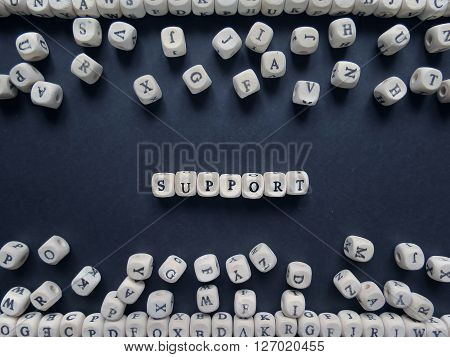 Word Support Of Small White Cubes Next To A Bunch Of Other Letters On The Surface Of The Composition