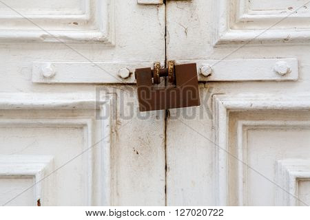 A withe wood door closed with a weathered rusty lock