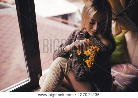 Portrait Of Young Beautiful Woman In Gray Pullover Sitting On Window Sill With Yellow Flowers