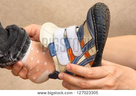 hands of mother helping her little daughter to put shoes closeup